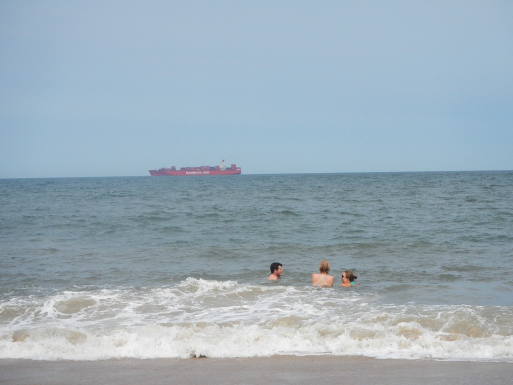 Karl, Nicole and Natalie swimming as a big ship sails up in to the Delaware Bay