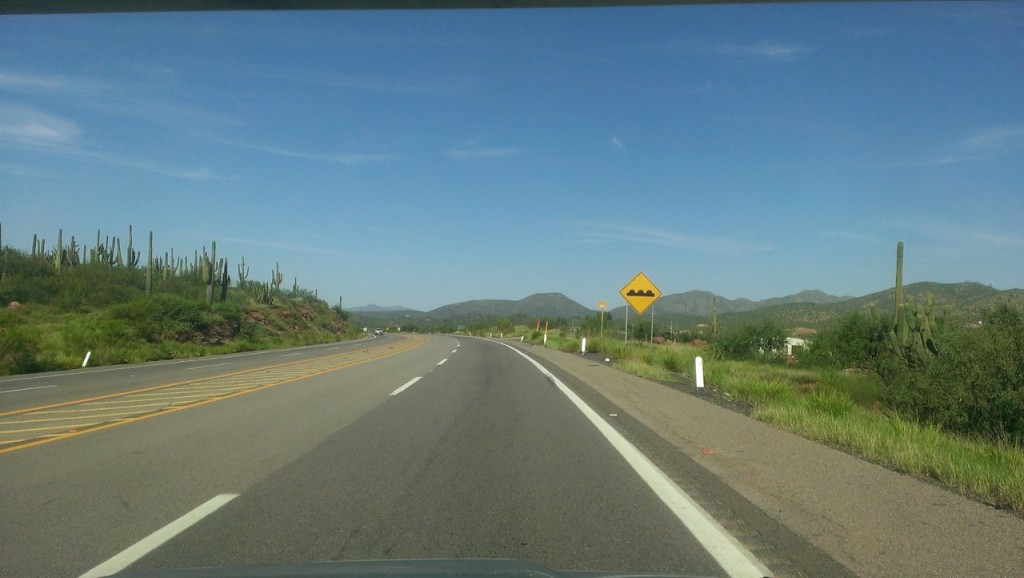 The two lane highway with a sign for topes, or bumps